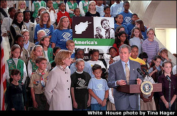 President George W. Bush speaking at an assembly of children and civic leaders.