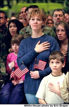 "Family members of Air Force personnel place their hands over their hearts at Elmendorf Air Force Base in Anchorage, Alaska, Feb. 16, 2002. ""I'm honored to be in a place where people understand the need for sacrifice and patriotism,"" said the President. ""And I've come to Alaska to let you know that I'm proud of our United States military; that when I sent you into action, I knew you would not let this nation down."