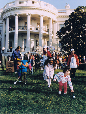 Youngsters at the White House Easter Egg Roll inch their eggs down the south lawn course toward the finish line under the watchful eyes of volunteers.