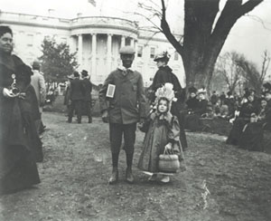 A young girl and her escort pose on the South grounds of the White House on Easter Monday, 1889.