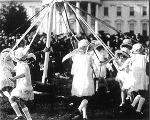 While wearing white dresses, girls dance around a maypole, a game introduced at the White House Easter Egg Roll by President and Mrs. Hoover.