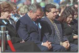President George W. Bush and Laura Bush bow their heads in prayer at the dedication ceremony for the Oklahoma City National Memorial February 19, 2001. (White House Photo by Paul Morse)