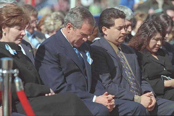 President George W. Bush and Laura Bush bow their heads in prayer at the dedication ceremony for the Oklahoma City National Memorial February 19, 2001.