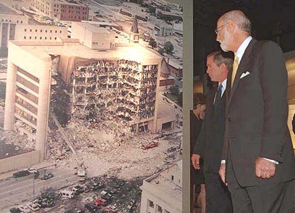 President George W. Bush looks at a photo of the Oklahoma City Murrah Federal Building bombing at the Oklahoma City National Memorial February 19, 2001.