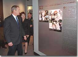 President George W. Bush and First Lady Laura Bush look at an exhibit showing the famous photo of a firefighter carrying a baby girl at the Oklahoma City Murrah Federal Building bombing at the Oklahoma City National Memorial February 19, 2001. The President attended the dedication ceremony of the memorial. (White House Photo by Paul Morse)