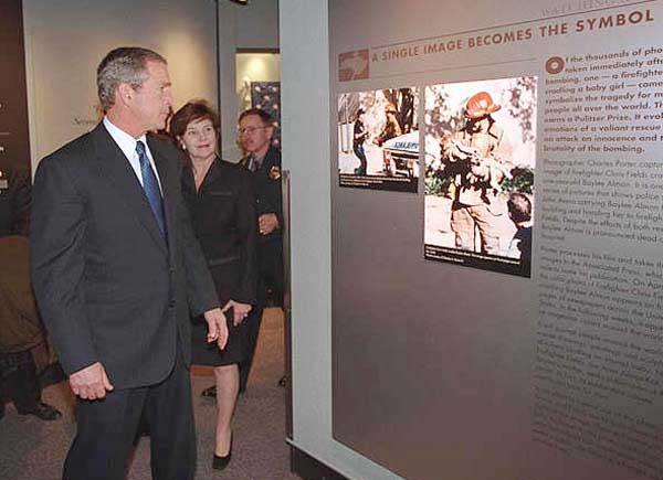 President George W. Bush and First Lady Laura Bush look at an exhibit showing the famous photo of a firefighter carrying a baby girl at the Oklahoma City Murrah Federal Building bombing at the Oklahoma City National Memorial February 19, 2001.