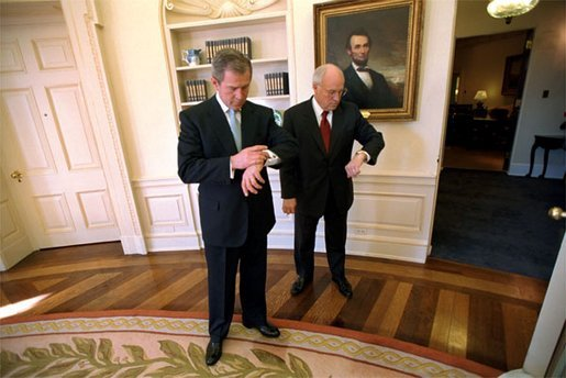 President George W. Bush and Vice President Cheney check the time after the swearing-in ceremony for Secretary of State Colin Powell in the Oval Office Jan. 26, 2001. White House photo by Eric Draper.