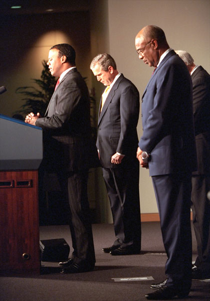 President George W. Bush bows his head as Rep. J.C. Watts, Jr. (R.-Okla.) leads a prayer before the swearing-in ceremony for Rod Paige, right, as Secretary of Education in the Barnard Auditorium at the Department of Education Jan. 24, 2001. White House photo by Eric Draper