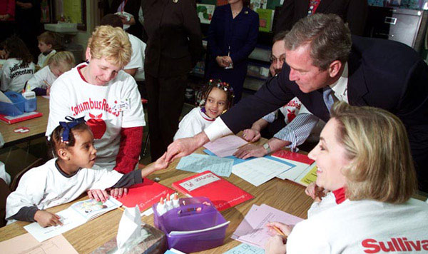 President George W. Bush greets a student at Sullivant Elementary School in Columbus Ohio on February 20, 2001. The president traveled to the school to emphasize accountability of school for the quality of education they provide. White House Photo by Paul Morse