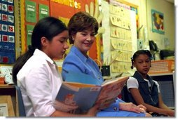 "Laura Bush listens as a student at Caesar Chavez Elementary School reads during a ""Ready to Read Ready to Learn"" visit to the school in Hyattsville, Maryland, Feb., 26, 2001."