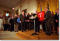 The Univerity of Oklahoma football team presents President George W. Bush with a jersey in the East Room of the White House on March 5, 2000. (WHITE HOUSE PHOTO BY ERIC DRAPER)