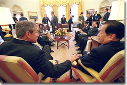 Pictured is President Bush talking with the Vice Premier of China Qian Qichen in the Oval Office. Both are seated in front of the mantel.