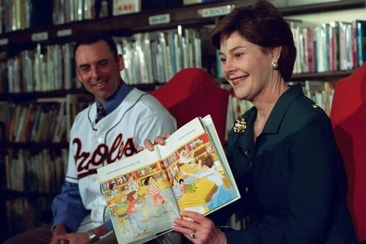"Laura Bush and Baltimore Orioles shortstop, Mike Bordick, read to children at the Washington, D.C. Public Library, Northeast Branch, as part of ""Celebrate National Library Week at your Library"" April 3, 2001. White House photo by Eric Draper."
