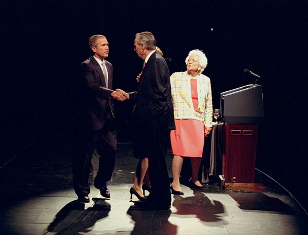 President George W. Bush shakes hands with his father, former president George Bush, as former first lady Barbara Bush looks on from the podium during a Celebration of Reading event Thursday, April 26, in Houston. WHITE HOUSE PHOTO BY PAUL MORSE