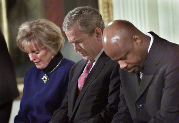 "President George W. Bush lowers his head in prayer between Shirley Dobson, left, and Rev Wintley Phipps during a reading of ""Our Nations Prayer"" at the White House reception for the 50th Anniversary of the National Day of Prayer. WHITE HOUSE PHOTO BY ERIC DRAPER"