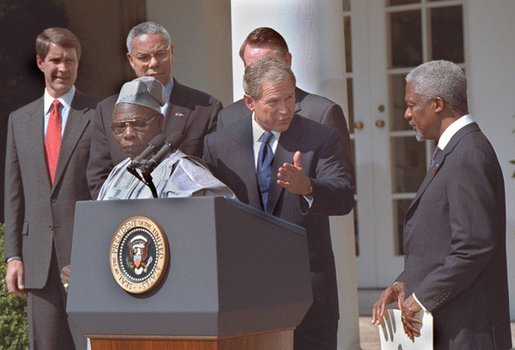 President George W. Bush welcomes UN Secretary General Kofi Annan to the podium after his announcement of Presidential HIV/AIDS Trust Fund Initiative as Nigerian President Olusegun Obsanjo looks on at left in the Rose Garden, Friday, May 11, 2001. White House photo by Eric Draper.