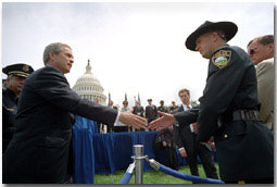 President George W. Bush greets a police officer from Flagstaff, AZ., after placing a wreath to commemorate the 20th Annual Peace Officers Memorial Service at the Capitol.