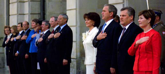 President George W. Bush and First Lady Laura Bush and the American delegation during the playing the American national anthem with the president of Poland Aleksander Kwasniewski and Mrs. Kwasniewski during an arrival ceremony at the Polish Presidential Palace