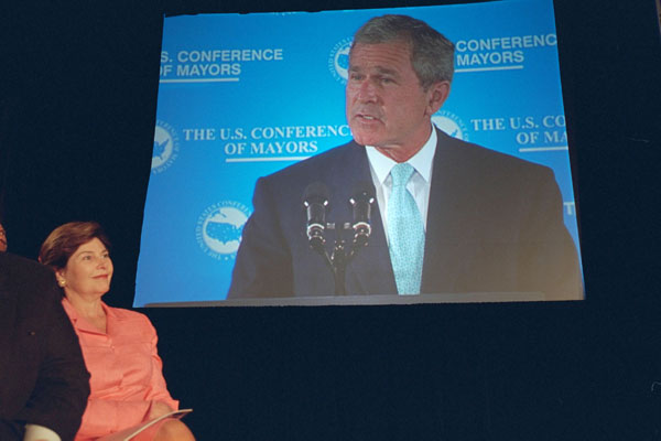 Laura Bush looks on in the audience as President George W. Bush is displayed on a giant screen monitor during his speech at the 69th Conference of Mayors in Detroit, Michigan, Monday, June 25, 2001. WHITE HOUSE PHOTO BY ERIC DRAPER