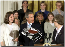 President George W. Bush holds a goalie glove with the