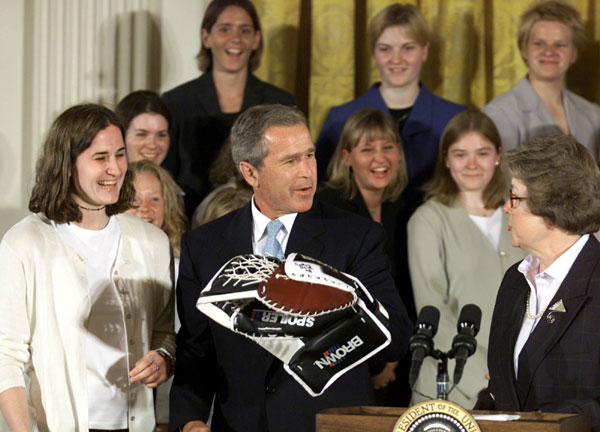 President George W. Bush holds a goalie glove with the team captain Brittny Ralph, left, and Chancellor Kathryn Martin of the Minnesota-Duluth 2001 NCAA Women's Hockey Champions Monday, June 25, 2001. WHITE HOUSE PHOTO BY PAUL MORSE