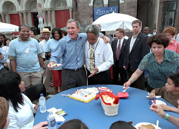 Arm in arm with Philadelphia Mayor John Street, President Bush passes out birthday cake at an urban block party in Philadelphia July 4, 2001. The President celebrates his 55th birthday July 6, 2001.