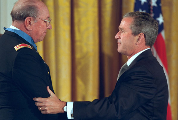 President Bush drapes the Congressional Medal of Honor on Ed Freeman of Boise, Idaho, in the East Room at the White House Monday, July 16, 2001. Mr. Freeman was awarded the honor for his actions in 1965 when, as a helicopter pilot during, he flew through gunfire more than 20 times during a single, ferocious battle, bringing supplies to a trapped batallion and flying more than 70 wounded soldiers to safety. White House photo by Paul Morse.