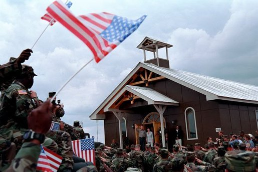 President George W. Bush and Laura Bush walk out of the chapel at Camp Bondsteel and are greeted by troops July 24, 2001 in Kosovo, Federal Republic of Yugoslavia. White House photo by Eric Draper.