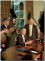 President Bush, Secretary of Energy Spencer Abraham (left) and economic advisor Larry Lindsey speak with the media in the Oval Office before the President signed an executive order that sets a standard of energy efficiency July 31, 2001.