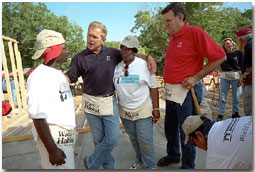 "President Bush and Secretary for Housing and Urban Development Martinez, far right, talk with new friends during a break from their house-building efforts at the Waco, Texas, location of Habitat for Humanity's ""World Leaders Build"" construction drive August 8, 2001. White House photo by Eric Draper."