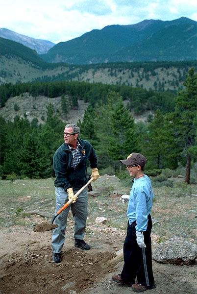 Working for his share of the picnic bounty, President Bush helps build a trail at Rocky Mountain National Park in Estes, Colo., Aug. 14. After sharing lunch with YMCA volunteers, the President addressed the media.