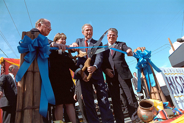 With help from officials from Albuquerque's Hispano Chamber of Commerce, President Bush cuts the ribbon to open the Barelas Job Oppurtinity Center Aug 15. White House photo by Moreen Ishikawa.