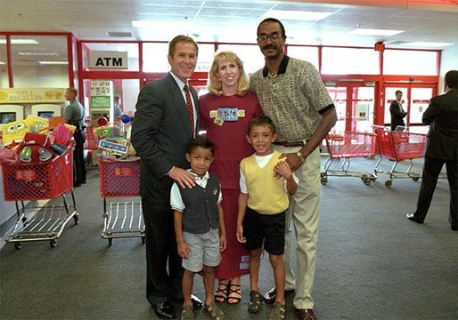 After talking with several families about how far $600 can go during family shopping trips, President Bush poses for pictures with one of the families just outside the Target Snack Bar at a retail location in Kansas City, Mo., Aug. 21, 2001. White House photo by Moreen Ishikawa.