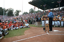 "President Bush kicks off the Little League World Series with a thank you to all the parents, coaches and volunteers who donate their time to childrens' sports during his induction ceremony into Little League's Hall of Excellence Aug. 26 in Williamsport, Pa. ""You prioritize your family and that's crucial for a healthy world, to make sure our families remain strong,"" said the President. ""I equate Little League baseball with good families."". White House photo by Moreen Ishikawa."