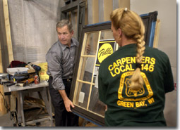 President George W. Bush assists a Union worker with the installation of a glass window frame during his tour of the Northern Wisconsin Regional Council of Carpenters Training Center in Kaukauna, WI., Monday, Sept. 3, 2001. WHITE HOUSE PHOTO BY ERIC DRAPER.
