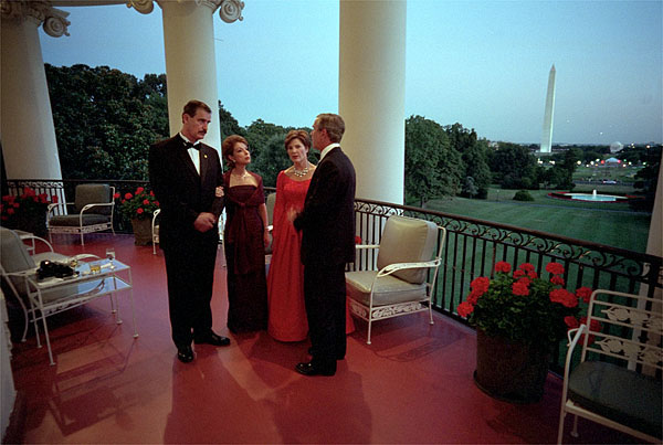 Mexican President Vicente Fox and his wife Martha Sahagun de Fox talk privately with President Bush and First Lady Laura Bush on the Truman Balcony of the White House before greeting guests at the state dinner Wednesday evening. After the dinner, the two couples and their friends watched fireworks from the balcony. White House photo by Eric Draper.