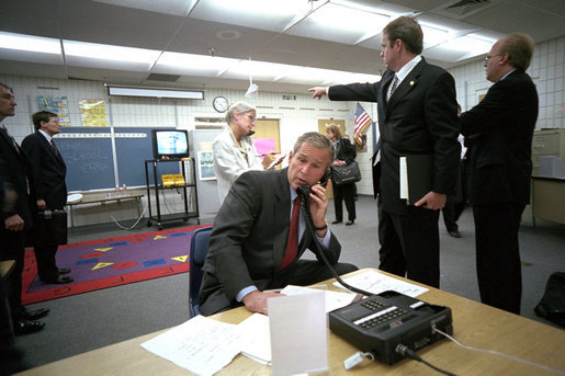 As Director of Communications Dan Bartlett points to news footage of the World Trade Center Towers burning, President George W. Bush gathers information about the attack at Emma E. Booker Elementary School in Sarasota, Fla., Sept. 11, 2001. Also photographed are Director of White House Situation Room, National Security Council, Deborah Loewer (directly behind the President) and Senior Advisor Karl Rove (right). White House photo by Eric Draper