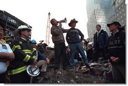 "Standing upon the ashes of the worst terrorist attack on American soil, Sept. 14, 2001, President Bush pledges that the voices calling for justice from across the country will be heard. Responding to the Presidents' words, rescue workers cheer and chant, ""U.S.A, U.S.A."" White House photo by Eric Draper"