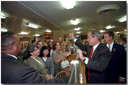 President George Bush gives a thumbs up to a crowded cafeteria while visiting the Pentagon September 17. After meetings, the President talked with hundreds of employees throughout the complex. White House photo by Eric Draper.