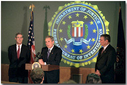 President Bush addresses the media during a tour of FBI headquarters with director Robert Mueller, left, and Attorney General John Ashcroft Sept. 25. The President visited the offices to personally thank employees for their recent and contined efforts since the Sept. 11 attack. White House photo by Paul Morse.