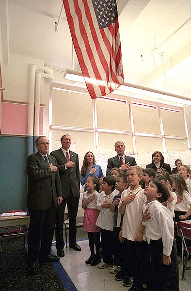 "Accompanied by a chorus of little and big voices, President Bush says ""The Pledge of Allegiance,"" at an elementary school during his visit to New York Oct. 3. White House photo by Paul Morse."