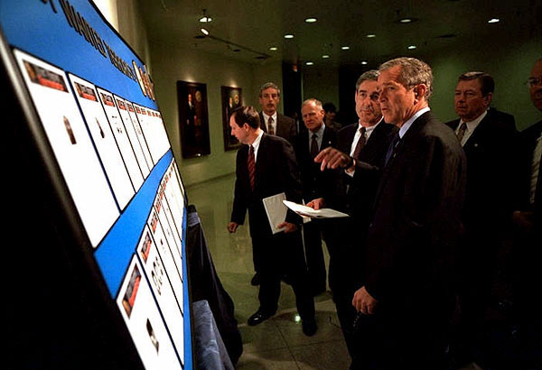 White House photo by Eric Draper. President George W. Bush looks over the newly created list of Most Wanted Terrorists with FBI Director Rober Mueller at the agency's headquarters Oct. 10.