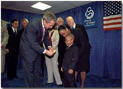 After presenting President George Bush with a pair of boots, March of Dimes Ambassador Justin Lamar Washington gives the President a dollar to help with contributions to the Afghan children during the organizations' Washington D. C. event Oct. 12. White House photo by Tina Hager.