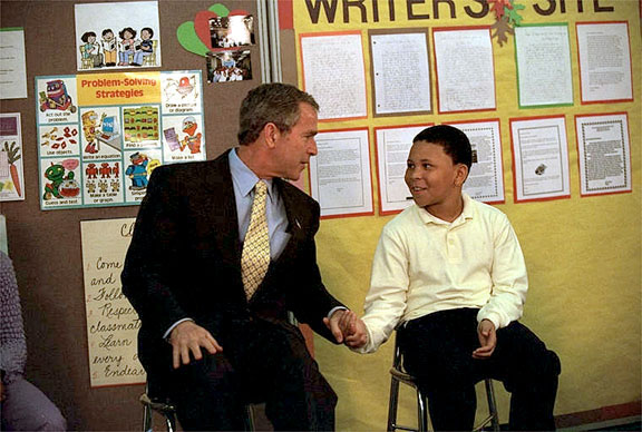 "President George W. Bush talks with a student at Thurgood Marshall Extended Elementary School, where he announced his initiative, Friendship Through Education, Oct. 25. ""We're going to ask schools all across the country to join with schools in other countries to spread the message that we care for each other, that we want to understand each other better,"" explained the President. White House photo by Eric Draper."