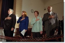 Laura Bush listens to the National Anthem with Bill and Elayne Bennett, left, and Secretary of Education Rod Paige, right, during a Best Friends for Our Children Event at Bertie Backus Middle School Nov. 7, 2001 in Washington, D.C.  White House photo by Susan Sterner