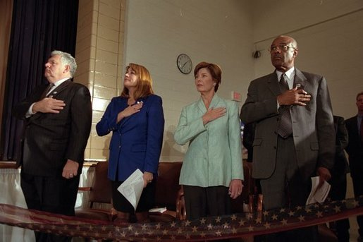 Laura Bush listens to the National Anthem with Bill and Elayne Bennett, left, and Secretary of Education Rod Paige, right, during a Best Friends for Our Children Event at Bertie Backus Middle School Nov. 7, 2001 in Washington, D.C. White House photo by Susan Sterner.