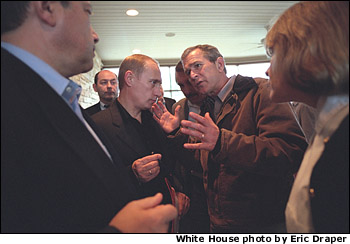 President George W. Bush and Russian President Vladimir Putin meet as Russian and White House staff listen moments before the departure of President and Mrs Putin from the Bush Ranch, Thursday, Nov. 15, 2001. White House photo by Eric Draper.