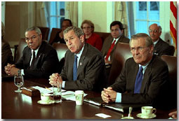 With Secretary of State Colin Powell and Secretary of Defense Donald Rumsfeld sitting at his side, President George W. Bush speaks with the media during a cabinet meeting Nov. 19. White House photo by Tina Hager.