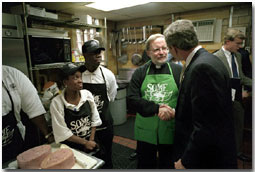Visiting the kitchen of So Others Might Eat charity, President George. W. Bush greets director Father Adams and other volunteers at the Washington D. C. site Nov. 20. Started in 1970, the program serves breakfast and lunch daily to homeless. White House photo by Tina Hager.