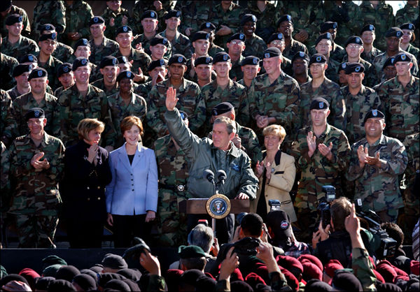 "Surrounded by cheering soldiers at Fort Campbell, Kentucky, President George W. Bush addressed the troops and shared a turkey dinner with them Nov. 21. ""More than 3,000 soldiers from this post have been deployed to Kosovo for six-month rotations,"" said the President. ""They kept supplies away from rebels in Macedonia, made the recent election in Kosovo possible. I'm glad to report that all of them from this base will be home by Thanksgiving."". White House photo by Tina Hager."
